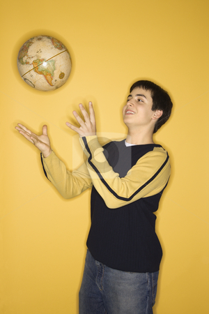 Teen boy tossing globe. stock photo, Portrait of smiling Caucasian teen boy tossing globe in air standing against yellow background. by Iofoto Images