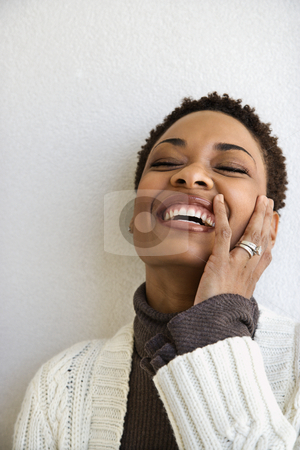 Happy laughing woman. stock photo, Close up head and shoulder of African-American woman standing against white wall smiling with hand on face and eyes closed. by Iofoto Images
