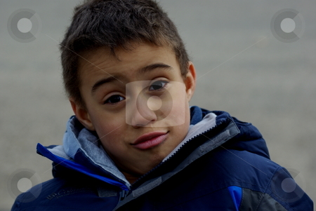 Portrait of a boy stock photo, A young boy's facial expression displays a variety of response from question to attitude during outdoor activity on a cold day. by Dennis Thomsen
