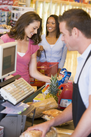 Woman paying for groceries stock photo, Woman paying for groceries at supermarket checkout by Monkey Business Images