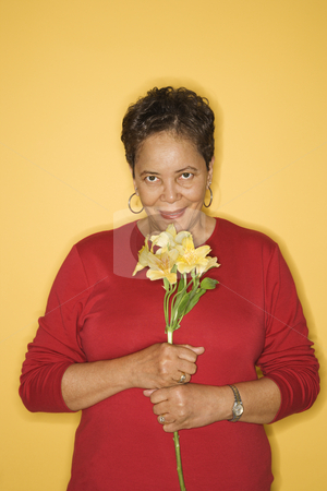 Woman smelling flowers. stock photo, African American mature adult female holding flowers. by Iofoto Images