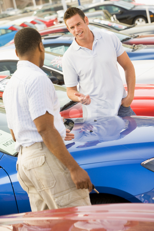 Man talking to car salesman stock photo, Man talking to car salesman on lot by Monkey Business Images