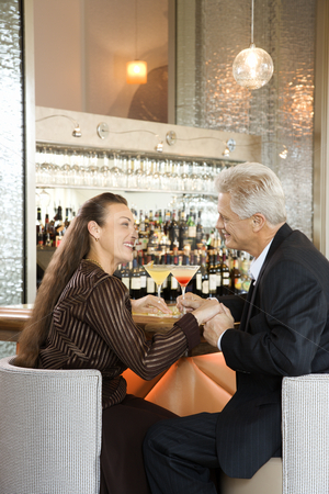 Couple sitting at bar. stock photo, Caucasian mature adult male and prime adult female sitting at bar holding hands. by Iofoto Images