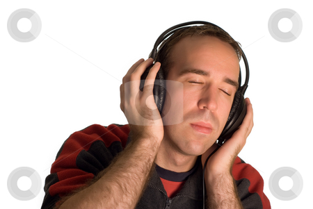 Man Wearing Headphones stock photo, A young man listening to music on a set of headphones, isolated against a white background by Richard Nelson