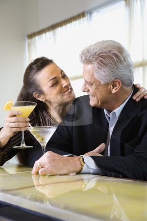Couple drinking at bar. stock photo, Caucasian mature adult male and prime adult female sitting at bar with cocktails. by Iofoto Images