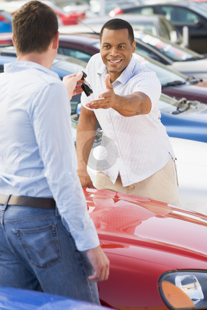 Man collecting new car from salesman stock photo, Man collecting new car from salesman on lot by Monkey Business Images