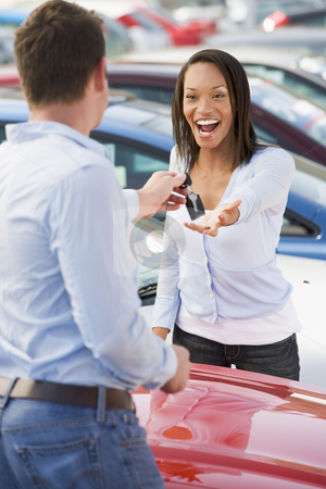 Woman collecting keys to new car stock photo, Woman collecting keys to new car from salesman by Monkey Business Images