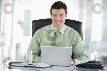 Businessman sitting in office with personal organizer using lapt stock photo,  by Monkey Business Images