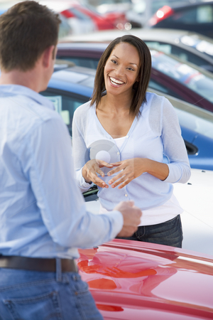 Young woman talking to car salesman stock photo, Young woman talking to car salesman in lot by Monkey Business Images