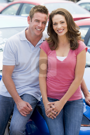 Young couple choosing new car stock photo, Young couple choosing new car on lot by Monkey Business Images