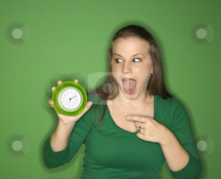 Woman pointing to clock. stock photo, Young female Caucasian adult holding and pointing to clock. by Iofoto Images