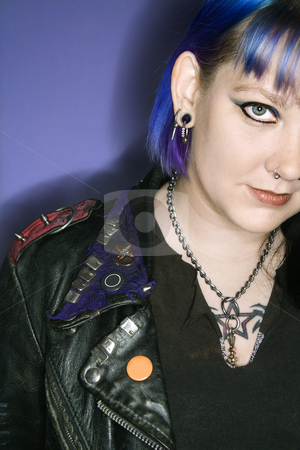 Woman in leather jacket. stock photo, Portrait of Caucasian woman with blue hair and black leather jacket against blue background. by Iofoto Images