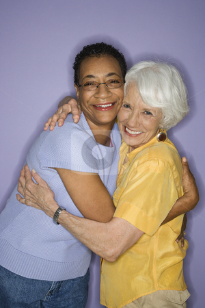 Women embracing. stock photo, Caucasian and African American mature adult female embracing. by Iofoto Images