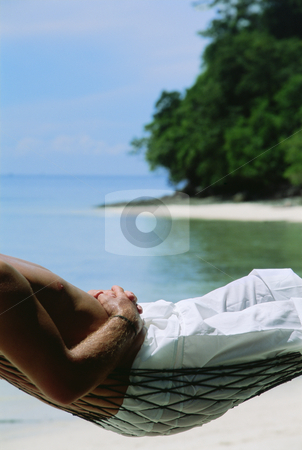Midsection of man lying in hammock at beach stock photo,  by Monkey Business Images
