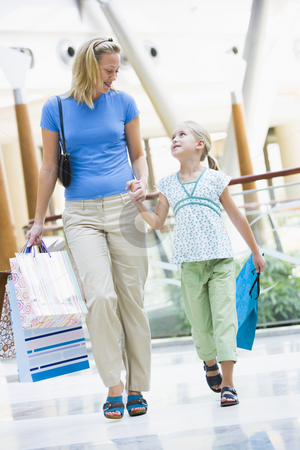 Mother and daughter shopping in mall stock photo, Mother and daughter shopping in mall carrying bags by Monkey Business Images