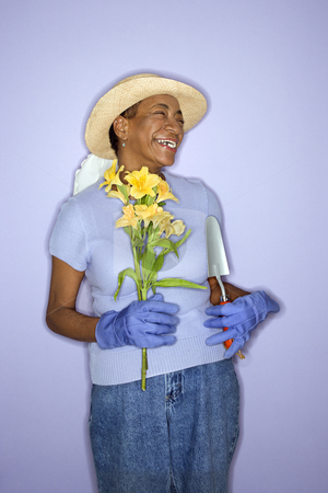 Happy gardener woman. stock photo, African American mature adult female with hand shovel and flowers. by Iofoto Images