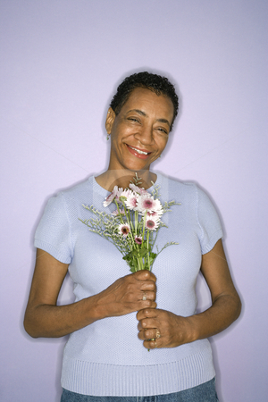 Woman holding flowers. stock photo, African American mature adult female holding flowers. by Iofoto Images