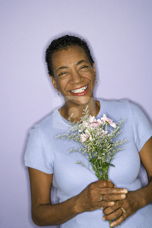 Smiling woman holding flowers. stock photo, African American mature adult female holding flowers. by Iofoto Images