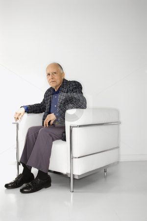 Man sitting in chair. stock photo, Caucasian mature adult male sitting in chair looking at viewer. by Iofoto Images