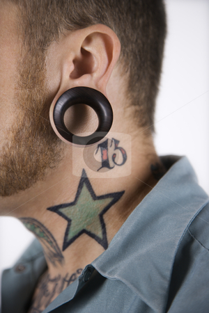Man with tattoos and piercings. stock photo, Caucasian mid-adult man with tattoos and piercings. by Iofoto Images