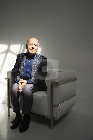 Man sitting in chair. stock photo, Caucasian mature adult male sitting in chair. by Iofoto Images