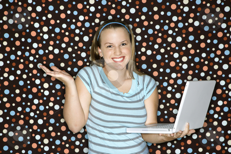 Woman holding laptop computer. stock photo, Young Caucasian woman holding laptop shrugging and smiling. by Iofoto Images