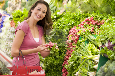 Woman shopping for produce in supermarket stock photo, Woman shopping for fresh produce in supermarket by Monkey Business Images