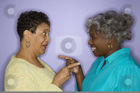 Women friends. stock photo, Mature adult African American females pointing at eachother. by Iofoto Images
