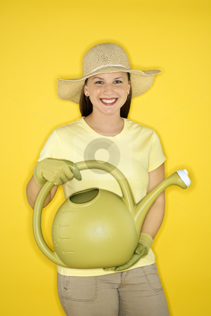 Smiling woman holding watering can. stock photo, Young adult female Caucasian holding watering can wearing straw hat. by Iofoto Images