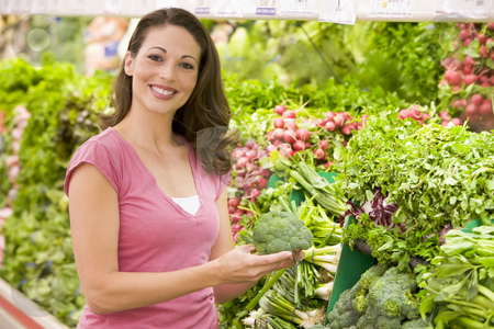 Woman shopping for vegetables in supermarket stock photo, Woman shopping for fresh vegetables in supermarket by Monkey Business Images