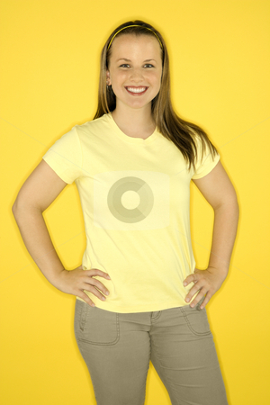 Portrait of smiling woman. stock photo, Young adult female Caucasian standing smiling on yellow background. by Iofoto Images