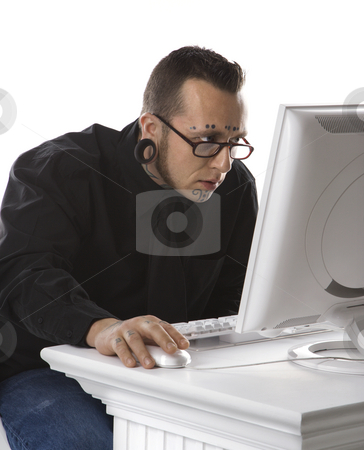 Adult male using computer. stock photo, Caucasian mid-adult man  with tattoos and piercings using computer. by Iofoto Images