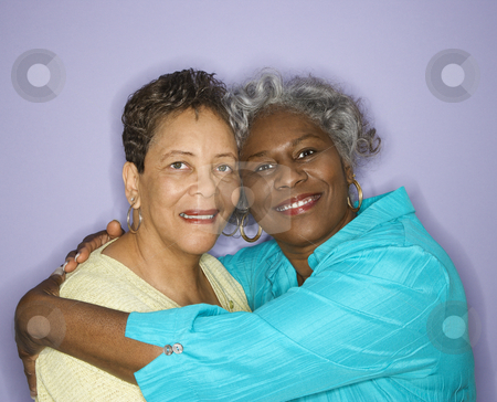 Women smiling and embracing. stock photo, Mature adult African American female looking at viewer smiling. by Iofoto Images