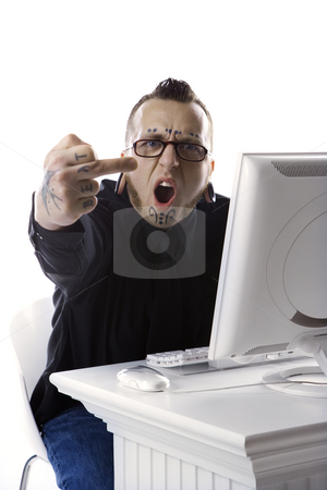 Man giving middle finger. stock photo, Caucasian  mid-adult man with tattoos and piercings using computer holding up middle finger. by Iofoto Images