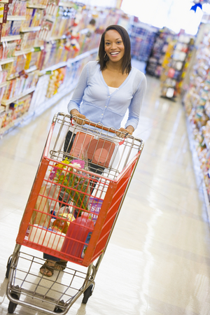 Young woman grocery shopping stock photo, Youing woman grocery shopping in supermarket by Monkey Business Images