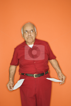 Man with empty pockets. stock photo, Mature adult Caucasian male pulling out empty pockets. by Iofoto Images