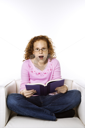 Girl reading book looking surprised. stock photo, Caucasian female child sitting reading book looking surprised. by Iofoto Images