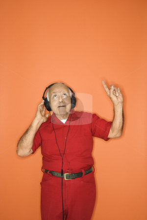 Man listening to headphones. stock photo, Mature adult Caucasian male listening to headphones. by Iofoto Images