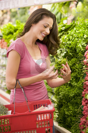 Young woman shopping for produce stock photo, Young woman shopping for produce in supermarket by Monkey Business Images