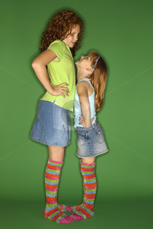 Girls standing face to face. stock photo, Caucasian female children standing face to face looking at each other. by Iofoto Images