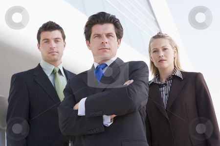 Three businesspeople standing outdoors by building stock photo,  by Monkey Business Images