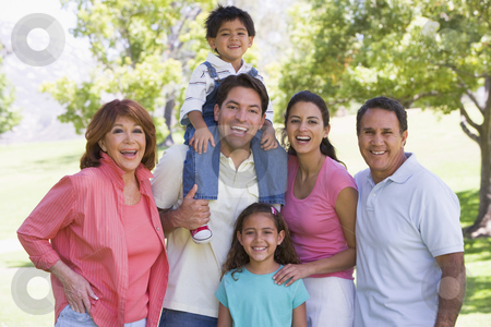 Extended family standing outdoors smiling stock photo,  by Monkey Business Images