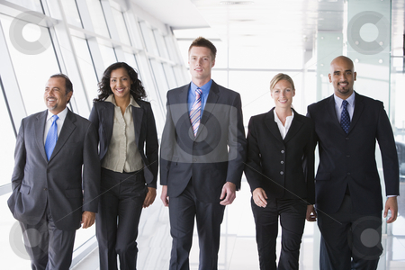 Group of business people walking towards camera stock photo, Group of business people walking through office towards camera by Monkey Business Images