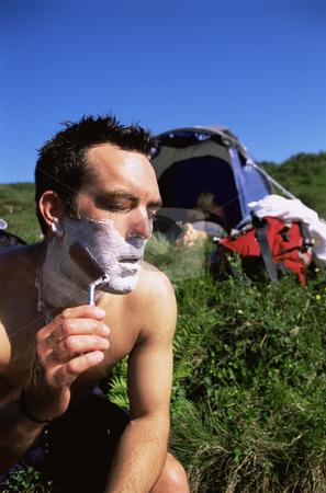 Man shaving in the outdoors next to tent stock photo,  by Monkey Business Images