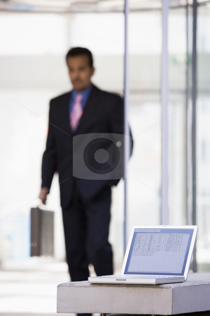 Laptop computer outside office stock photo, Laptop computer outside office with businessman in background by Monkey Business Images