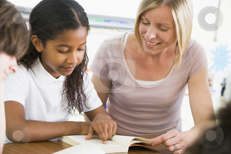 A schoolgirl and her teacher reading a book in class