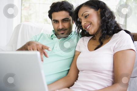 A Middle Eastern couple sitting with a laptop stock photo,  by Monkey Business Images