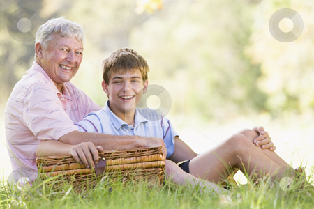Grandfather and grandson at a picnic smiling stock photo,  by Monkey Business Images