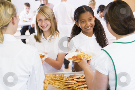 Lunchladies serving plates of lunch in school cafeteria stock photo,  by Monkey Business Images