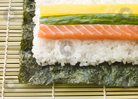 Making Rolled Sushi in a Sushi Mat stock photo, Making Rolled Sushi in a bamboo Sushi Mat by Monkey Business Images